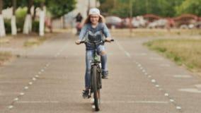 Une fille de onze ans dans une bonne humeur monte une bicyclette et après qu'un arrêt montre des pouces- banque de vidéos