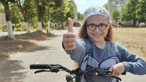 Une fille de onze ans dans une bonne humeur monte une bicyclette et après qu'un arrêt montre des pouces- clips vidéos