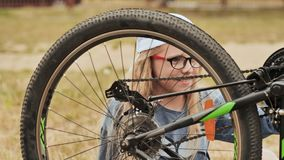 Une fille de onze ans tord et regarde la roue de sa bicyclette clips vidéos