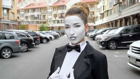 Une fille de pantomime dans un manteau de robe noir pose pour la caméra banque de vidéos