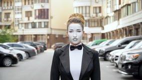 Une fille de pantomime dans un manteau de robe noir pose pour la caméra clips vidéos