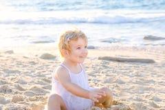 Une fille de sourire adorable mignonne d'enfant en bas âge dans des vêtements blancs jouant avec le sable et les coquilles sur la Photo stock