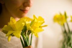 Une fille de sourire avec un bouquet de ressort jaune fleurit, narcisse images libres de droits