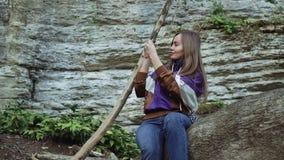 Une fille de sourire dans une veste de sport s'assied sur un arbre dans les montagnes et prend la photo au téléphone banque de vidéos