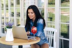 Une fille de sourire gaie s'assied à une table dans un café, conduit la correspondance importante sur son ordinateur portable dan photos libres de droits