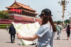 Une fille de touristes tient une carte de capitale de la Chine Pékin photographie stock
