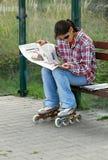 Une fille dedans en ligne à un arrêt d'autobus lit un journal photographie stock libre de droits