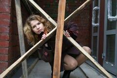 Une fille derrière les barrières en bois Images stock