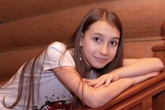 Une fille des repos européens d'aspect sur un escalier en bois dans une cabane en rondins photographie stock