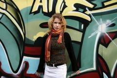 Une fille devant un mur de graffiti Photographie stock libre de droits