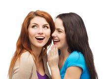 Une fille disant un autre secret Image stock