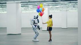 Une fille donne des ballons à un cyborg dans un hall vide banque de vidéos