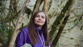 Une fille douce dans une veste colorée regarde les arbres couverts de mousse dans la forêt de conte de fées banque de vidéos