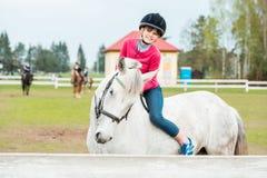 Une fille douce montant un cheval blanc, un athlète s'est engagée dans des sports équestres, des étreintes d'une fille et des bai Photos stock