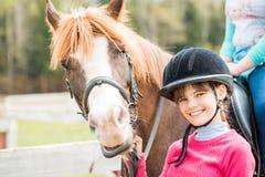 Une fille douce montant un cheval blanc, un athlète s'est engagée dans des sports équestres, des étreintes d'une fille et des bai Image stock