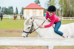 Une fille douce montant un cheval blanc, un athlète s'est engagée dans des sports équestres, des étreintes d'une fille et des bai Photo stock