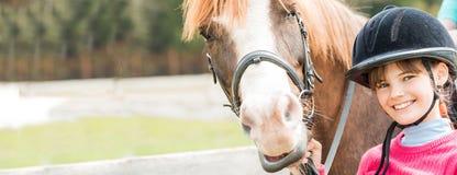 Une fille douce montant un cheval blanc, un athlète s'est engagée dans des sports équestres, des étreintes d'une fille et des bai Images libres de droits