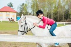 Une fille douce montant un cheval blanc, un athlète s'est engagée dans des sports équestres, des étreintes d'une fille et des bai Photo libre de droits