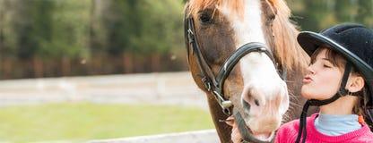 Une fille douce montant un cheval blanc, un athlète s'est engagée dans des sports équestres, des étreintes d'une fille et des bai Photographie stock