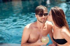 Une fille embrasse un type s'asseyant ensemble par la piscine Photo libre de droits