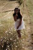 Une fille en pissenlit de soufflement de robe blanche image libre de droits