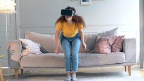 Une fille en VR-verres est les mains mobiles et se lever banque de vidéos