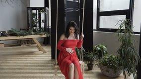 Une fille enceinte avec du charme dans une longue robe rouge balançant sur l'oscillation et touchant son ventre Conception de gro banque de vidéos