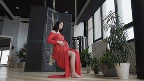 Une fille enceinte dans une longue robe rouge s'assied sur l'oscillation et frotte doucement son ventre et le regarde Conception  clips vidéos