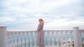 Une fille enceinte se tient sur le balcon à côté de la mer et caresse son ventre 4K banque de vidéos