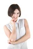 Une fille espiègle Une dame de brune d'isolement sur un fond clair Une jeune femme communicative Fille de sourire mordant son doi photo stock