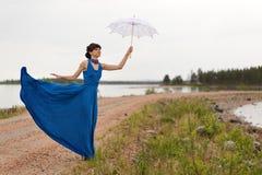 Une fille essaye de garder un parapluie photo libre de droits