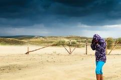 Une fille essaye de se cacher d'un vent violent Photos stock