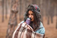 Une fille est couverte dans un plaid brun et boit d'une tasse thermo dans la forêt d'automne photos stock