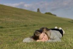 Une fille est décontractée sur l'herbe et fait fermer ses yeux photographie stock libre de droits