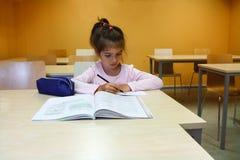 Une fille est dans la classe et apprenant à lire et écrire avec un crayon, elle écrit avec un stylo dans son carnet Photos stock