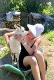 Une fille et une jeune chèvre s'asseyent dans une brouette pour le transport des marchandises Sentiments d'offre d'exposition images libres de droits