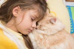 Une fille et un chat dorment gentiment dans le lit Photos stock
