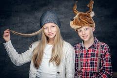 Une fille et un garçon dans des chapeaux de Noël Photo stock