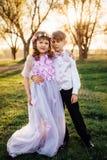 Une fille et un garçon dans des vêtements intelligents marchent en parc Images stock