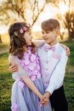 Une fille et un garçon dans des vêtements intelligents marchent en parc Photos libres de droits