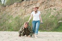 Une fille et un garçon jouant sur une plage Image stock