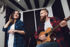Une fille et un type chantent une chanson à une guitare dans un studio d'enregistrement moderne photo stock