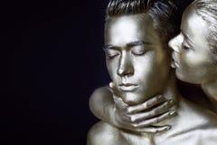 Une fille et un type couverts en peinture argentée Mes yeux étant fermé La fille s'est penchée dedans et embrasse son oreille Photo stock