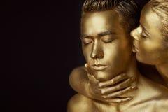 Une fille et un type couverts en peinture d'or Mes yeux étant fermé La fille s'est penchée dedans et embrasse son oreille Image stock