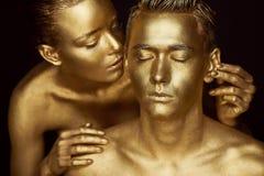 Une fille et un type couverts en peinture d'or Mes yeux étant fermé La fille s'est penchée dedans et embrasse son oreille Photographie stock