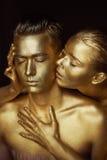Une fille et un type couverts en peinture d'or Mes yeux étant fermé La fille s'est penchée dedans et embrasse son oreille Photos stock