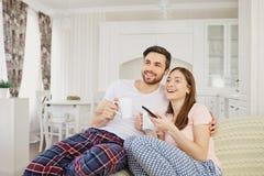 Une fille et un type regardent la TV se reposer sur le sofa dans la chambre image stock