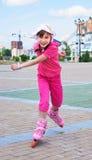 Une fille exécutant rapidement sur des patins de rouleau Photographie stock libre de droits