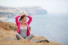 Une fille exécute des exercices de détente sur la plage Image libre de droits