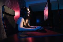 Une fille féminine mignonne de gamer s'assied dans une salle confortable derrière un ordinateur et joue des jeux Vidéo coulante v photos libres de droits